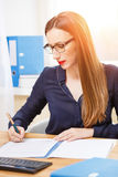 Young businesswoman working in office with papers. Young businesswoman working in office at sunny day with documents Stock Image