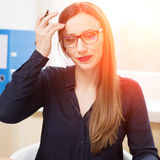 Young businesswoman working in office with papers. Young businesswoman working in office at sunny day with documents. Doubtful office female worker in glasses Stock Photos