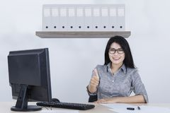 Young businesswoman showing OK sign. Young businesswoman working in the office while showing OK sign with her thumb Stock Photography