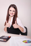 Young Businesswoman Working In Office And Showing Thumb Up Sign. Businesswoman Working In Office And Showing Thumb Up Sign stock image