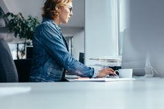 Young businesswoman working in office. Side view of young businesswoman working in office. Female designer sitting and using laptop Royalty Free Stock Photo