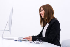 Young businesswoman working at office. Side view portrait of a young businesswoman working at office Royalty Free Stock Photography