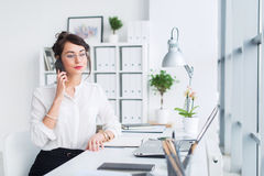 Young businesswoman working in office, typing, using computer. Concentrated woman searching information online stock photography