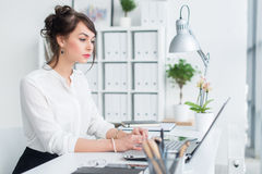 Young businesswoman working in office, typing, using computer. Concentrated woman searching information online.  Royalty Free Stock Photos