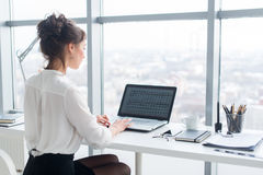 Young businesswoman working in office, typing, using computer. Concentrated woman searching information online, rear