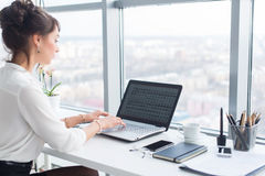 Young businesswoman working in office, typing, using computer. Concentrated woman searching information online, rear stock photos