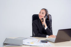 Young businesswoman working in office. Young businesswoman working in office, typing, using computer and talking phone - Concentrated woman searching Royalty Free Stock Photos