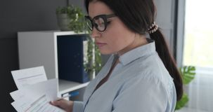 Young businesswoman working at office. Young businesswoman doing paperwork at office stock video footage