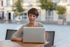 Young businesswoman working outdoors on a laptop Royalty Free Stock Photos