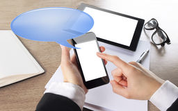 Young businesswoman working on smart phone with chat bubble icon Royalty Free Stock Images