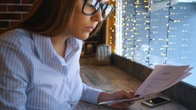 A young businesswoman works in a cafe and looks at the documents. Happy woman using laptop at cafe. Young beautiful girl sitting in a coffee shop and working on stock footage