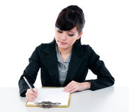 Young Businesswoman Writing On Clipboard Royalty Free Stock Photo