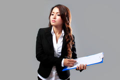 Young businesswoman writing on a clipboard while thinking Stock Photos