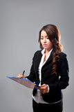 Young businesswoman writing on a clipboard while thinking Stock Images
