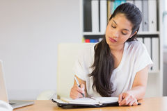 Young businesswoman writing in diary Royalty Free Stock Image
