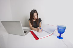 Young businesswoman. Writing on diary at office desk royalty free stock photo