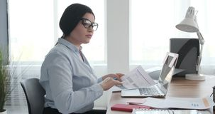Businesswoman working on reports at office. Young businesswoman writing on documents at office desk stock video