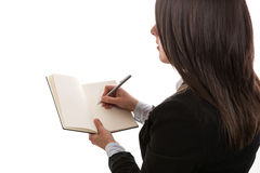 Young businesswoman writing in notebook. Isolated Stock Image