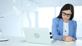 Young Businesswoman Writing in Office, Documentation royalty free stock photo