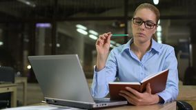 Young businesswoman writing startup ideas into notebook, planning meeting stock footage
