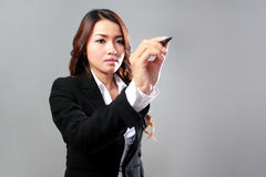 Young businesswoman writing on a virtual screen. A portrait of a young businesswoman working on a virtual screen stock photography