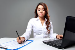 Young businesswoman writing while working with a laptop. A portrait of a young businesswoman writing while working with a laptop stock photography