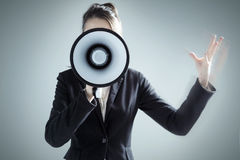Young businesswoman yelling over megaphone Stock Photography