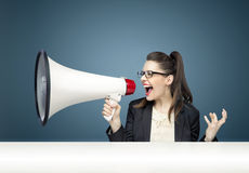 Young businesswoman yelling over megaphone Royalty Free Stock Photos