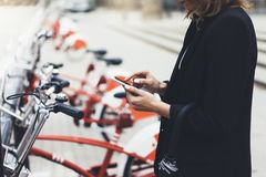 Young businesswomen in black suit and umbrella using smartphone, biking and going to work by city bicycle on urban street, hipster royalty free stock image