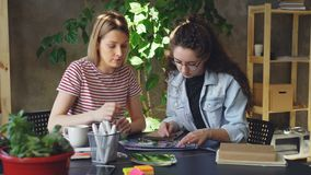 Young businesswomen designers are sitting together at table, talking and choosing pictures for new project. They are. Young attractive businesswomen designers in stock video footage