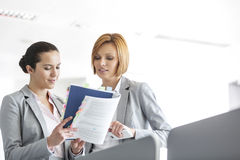 Young businesswomen discussing over book in office Royalty Free Stock Photography