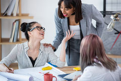 Young businesswomen discussing project and working with blueprint in office. Smiling young businesswomen discussing project and working with blueprint in office Stock Photo
