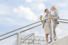 Young businesswomen with disposable coffee cups standing by railing against sky Royalty Free Stock Photography