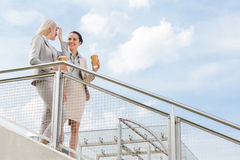 Young businesswomen with disposable coffee cups standing by railing against sky Stock Photo