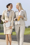 Young businesswomen with disposable cup and laptop walking on street Stock Photography