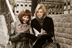 Two young fashion businesswomen with a folder Royalty Free Stock Photography