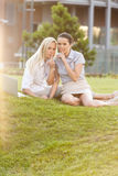 Young businesswomen gesturing silence in office lawn Stock Photo