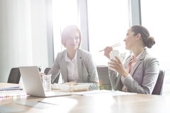 Young businesswomen having lunch at table in office Royalty Free Stock Photography