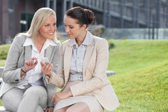 Young businesswomen with mobile phone sitting against office building Stock Photos