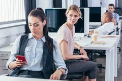 Young businesswomen in office. Young businesswoman using smartphone while colleagues sitting behind Stock Image