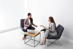 Free Young Businesswomen Sitting In Armchairs At Table Royalty Free Stock Images - 163923159