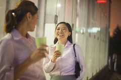 Young businesswomen smiling and drinking coffee outdoors at night Royalty Free Stock Photo