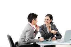 Young businesswomen talking. Young businesswomen sitting at office desk, looking at each other, smiling. Isolated on white Stock Photo