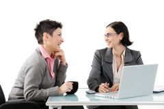 Young businesswomen talking. Young businesswomen sitting at office desk, looking at each other, smiling. Isolated on white Royalty Free Stock Photography