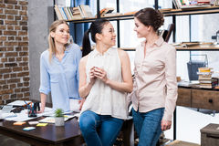 Young businesswomen talking at workplace while having coffee break Stock Photo