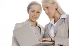 Young businesswomen using laptop against clear sky Royalty Free Stock Image