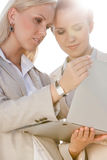 Young businesswomen using laptop against sky stock images