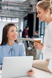 Young businesswomen using laptop and talking at workplace Stock Photography