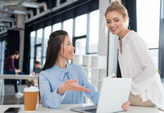 Young businesswomen using laptop and talking at workplace Stock Images