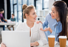 Young businesswomen using laptop and talking at workplace Royalty Free Stock Photo